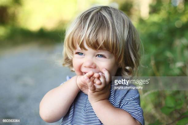 Child giggling covering his mouth