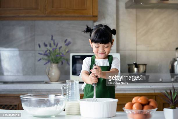 child girl enjoy cooking in the kitchen. happy asian kid is preparing the dough, bake cookies in the kitchen. - solo una bambina femmina foto e immagini stock