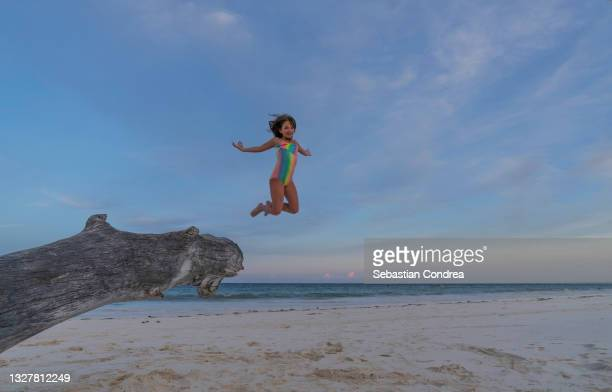 child girl jumping into the air off a tree trunk at the beach diani, indian ocean, kenya, africa. - mombasa stock pictures, royalty-free photos & images