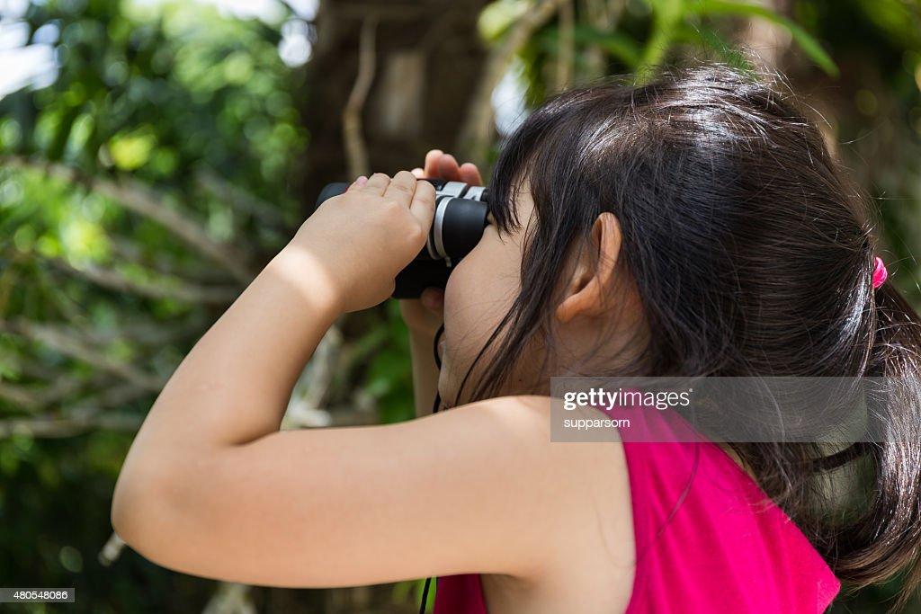 Criança menina, olhando através de binóculos : Foto de stock