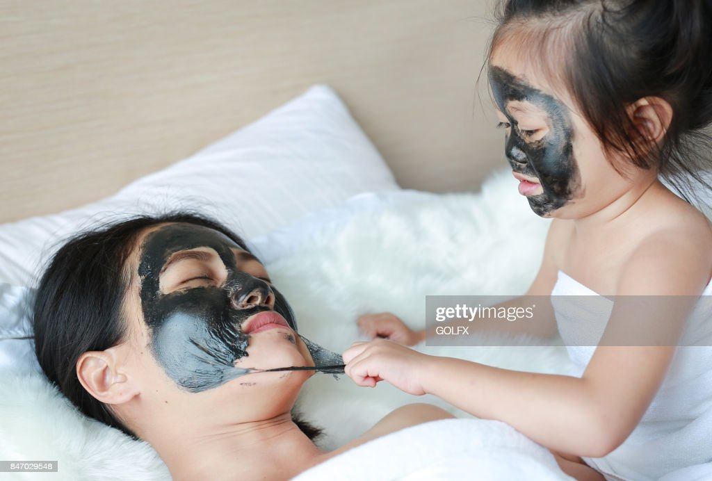 Child girl removed black mask from her mother, clean face. : Stock Photo