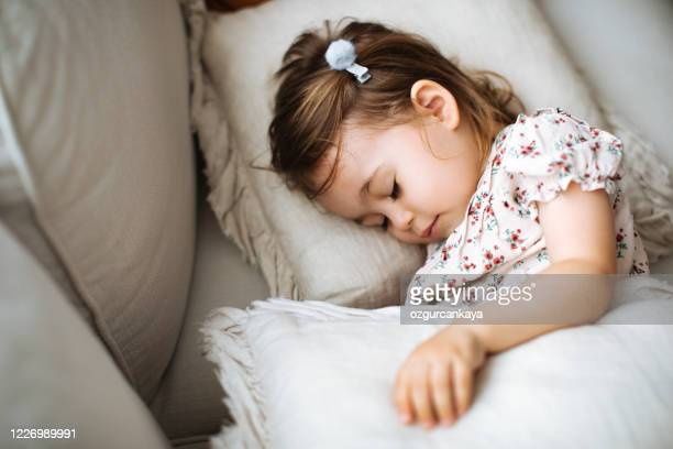 child girl sleeps in her bed with toy teddy bear - pillow stock pictures, royalty-free photos & images