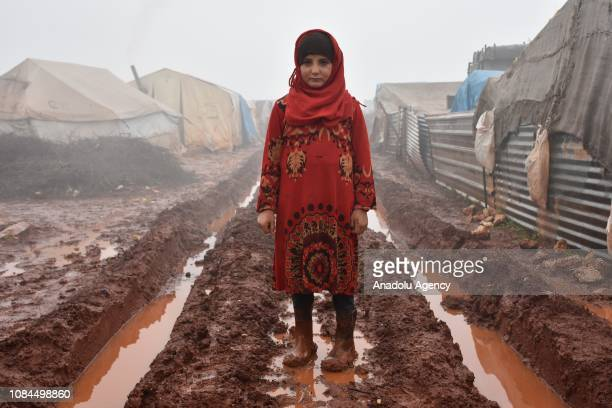 A child girl standing in the mud outside her shelter at AlIhsan refugee camp as Syrians enduring harsh winter at the camp in Idlib Syria on January...