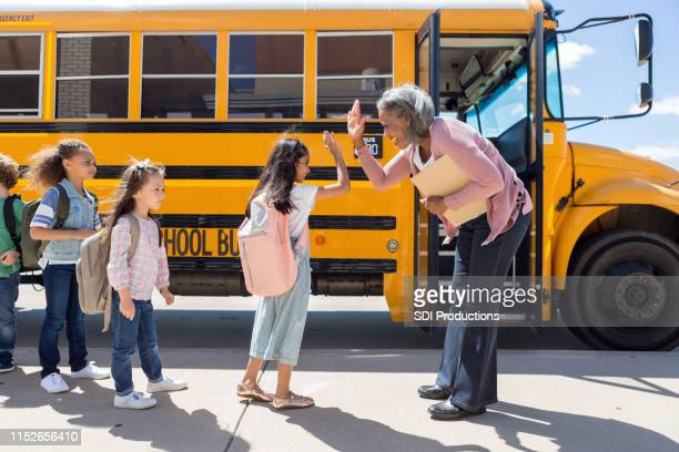 child gives school bus driver a high-five - school principal stock pictures, royalty-free photos & images