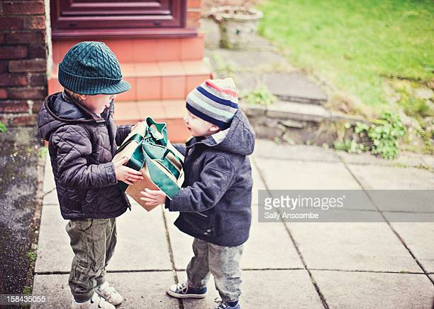 child giving a present to his little brother - giving stock pictures, royalty-free photos & images