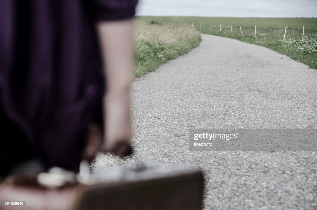 Child goes on the road with her suitcase : Stock Photo