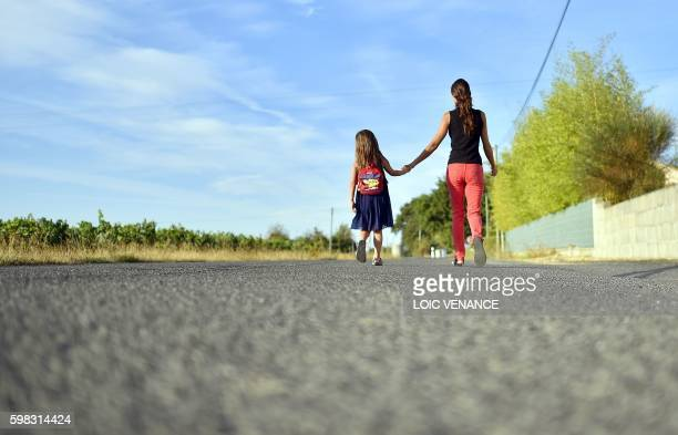 Child goes to school with her mother on September 1, 2016 in Vertou, western France, for the start of the school year. After two months of vacation,...
