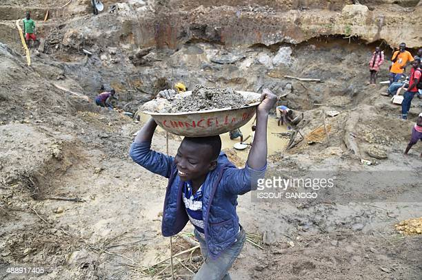 A child gold miner holds a bowl of earth on his head on May 5 2014 while looking for gold in a traditional mine in the village of Gam where gold...