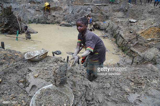 A child gold miner works on May 5 2014 while looking for gold in a traditional mine in the village of Gam where gold mining in the main business...
