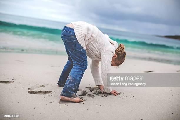 Child grabbing sand on beach, Australia