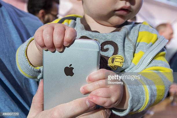 A child grasps a new Apple Inc iPhone 6s Plus at an Apple store in Palo Alto California US on Friday Sept 25 2015 From Sydney to New York some of the...