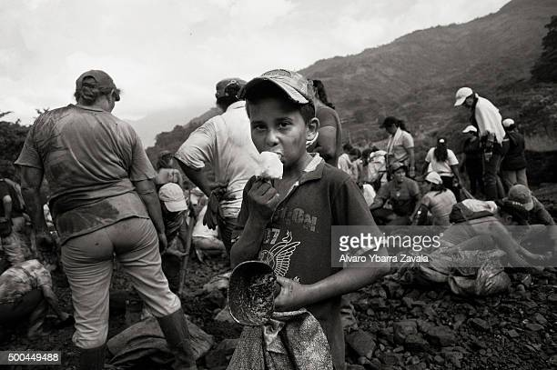 A child guaquero eats an ice cream as he takes a break from working in the washing area where the owners of the mine throw the discarded washed rocks...