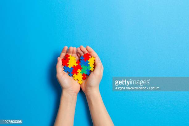 child hand holding colorful heart on blue background. world autism awareness day concept - learning disability stock pictures, royalty-free photos & images