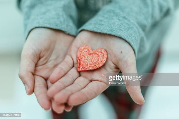 child hand holding red heart - woman giving birth stock photos and pictures