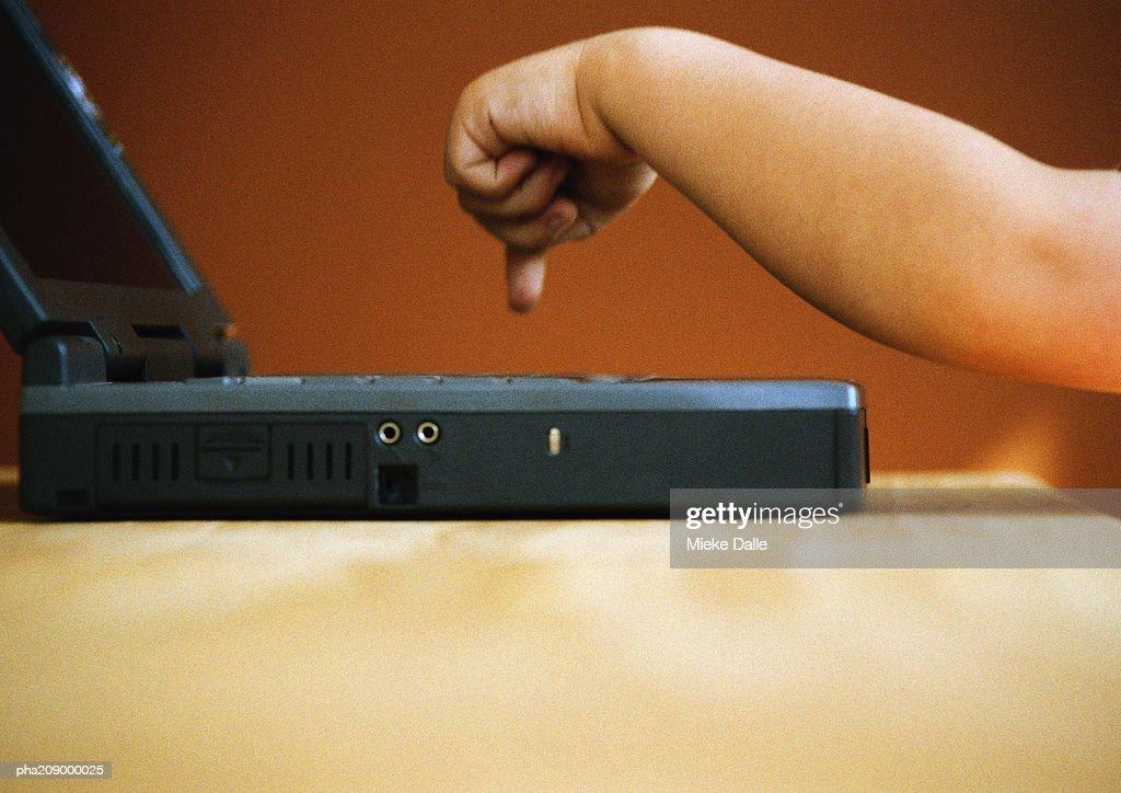 Child, hand pressing the keys of a laptop. : Stockfoto