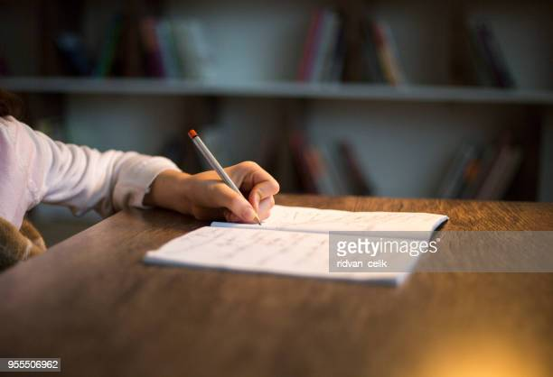 Kinderhand mit Bleistift zu üben auf ein Buch zu schreiben.