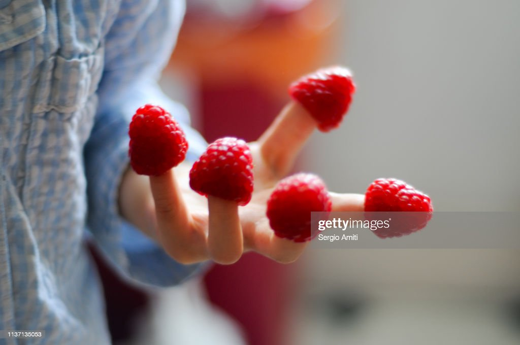 Child hand with raspberries on fingers : Stock Photo