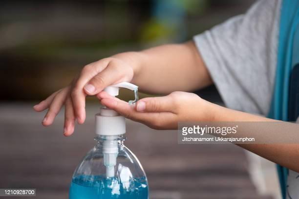 child hands using wash hand sanitizer gel. - alcool gel imagens e fotografias de stock