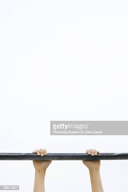 Child hanging on to metal bar, cropped view of hands