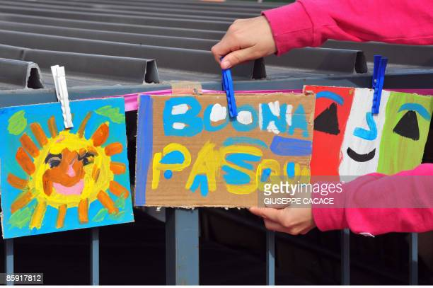 """Child hangs paintings reading """"Happy Easter"""" on Easter in a tent city for people evacuated after the April 6 earthquake on April 12,2009 in L'Aquila...."""