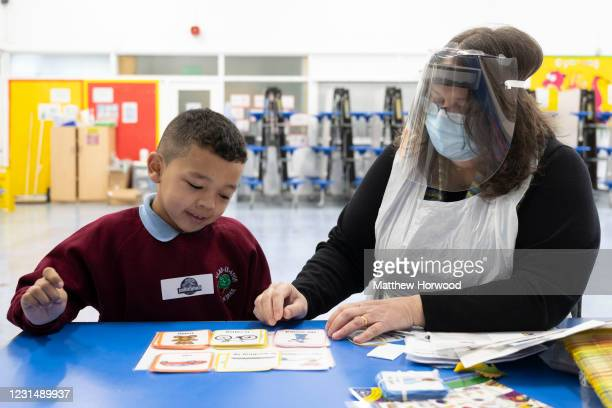 Child has a reading lesson with a teaching assistant wearing a face mask and visor at Glan-Yr-Afon primary school on March 3, 2021 in Cardiff, Wales....