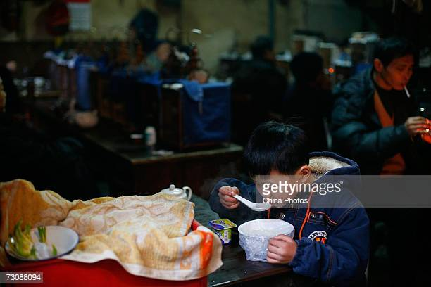 Child has breakfast at a Laohuzao teahouse at an alleyway January 23, 2007 in Shanghai, China. Laohuzao is a traditional store which sells hot water...