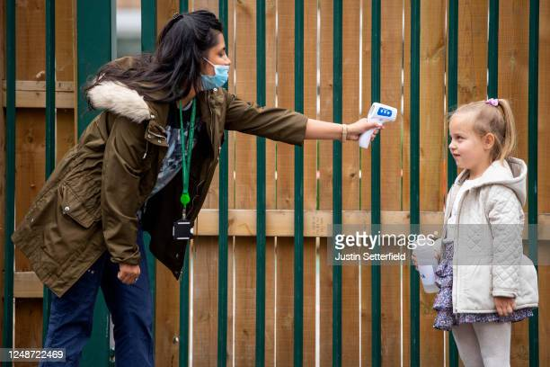 Child has her temperature checked by a teacher before entering Earlham Primary School, which is part of the Eko Trust on June 10, 2020 in London,...
