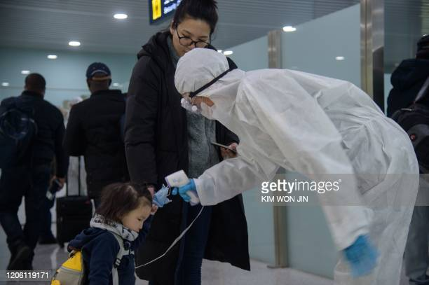 A child has her temperature taken as foreign diplomats and embassy staff prepare to board a flight to Vladivostok at Pyongyang International Airport...