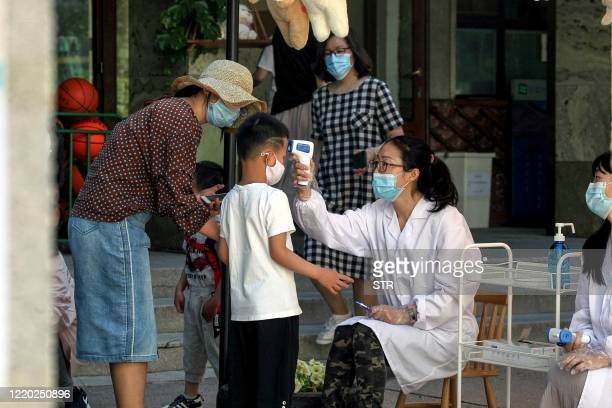 A child has his teperature checked before entering a kindergarten as kindergartens reopen in Shenyang in China's northeastern Liaoning province on...