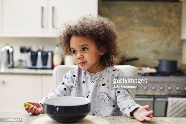 child having breakfast in the kitchen - one girl only stock pictures, royalty-free photos & images