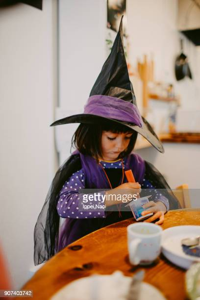 Child having breakfast with halloween witch costume