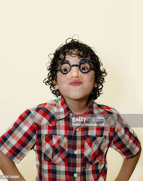 Child having fun and making faces while wearing glasses with a false nose in front of a white background