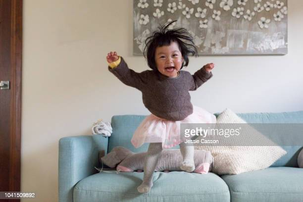 child having fun jumping off sofa - criança pequena - fotografias e filmes do acervo