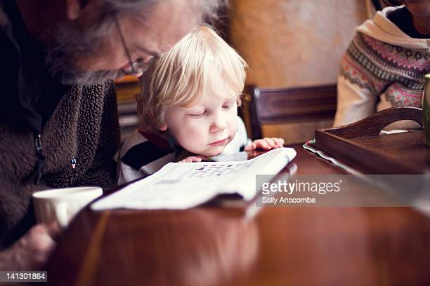 child helping his grandpa do crossword - news not politics stock pictures, royalty-free photos & images