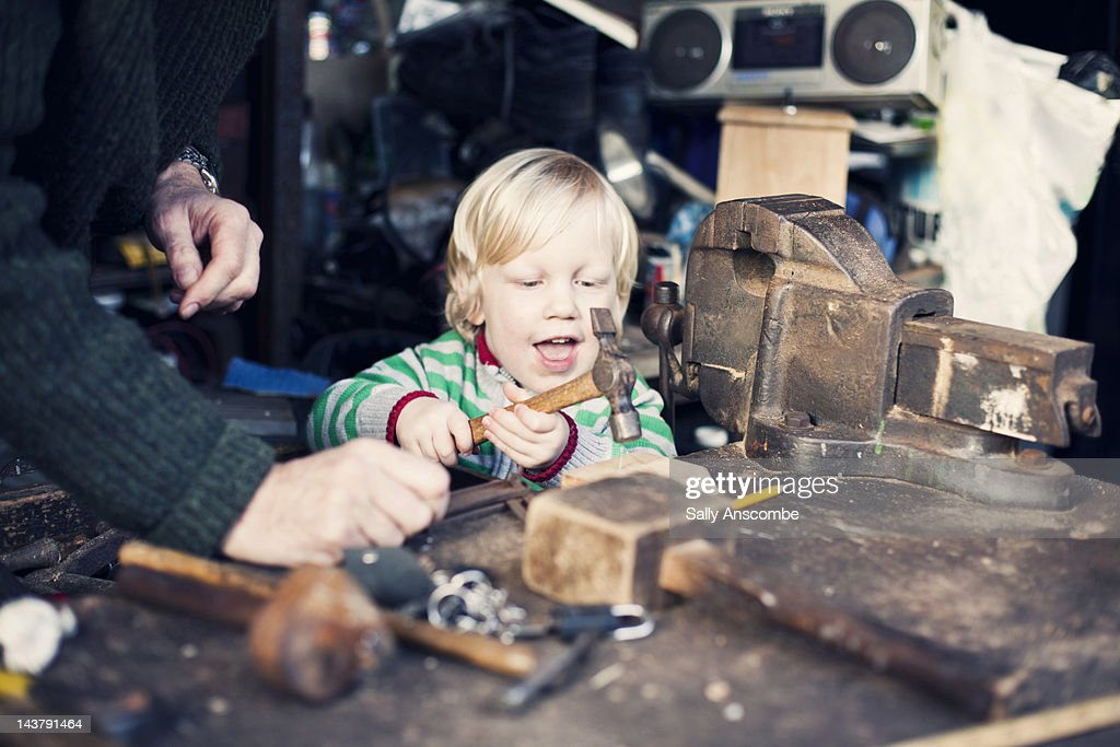 Little boy using hammer while helping his grandpa at work bench.