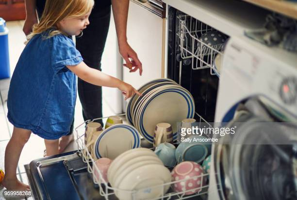 child helping to load the dishwasher - appliance fotografías e imágenes de stock
