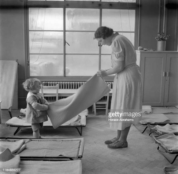 Child helping with the chores at a day nursery in the Social Centre in Slough, Berkshire, England, during World War II, November 1940.