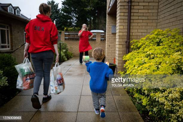 Child helps a member of staff to carry food donations from his family at the Cooking Champions food bank in Grange Park, north London on October 27...