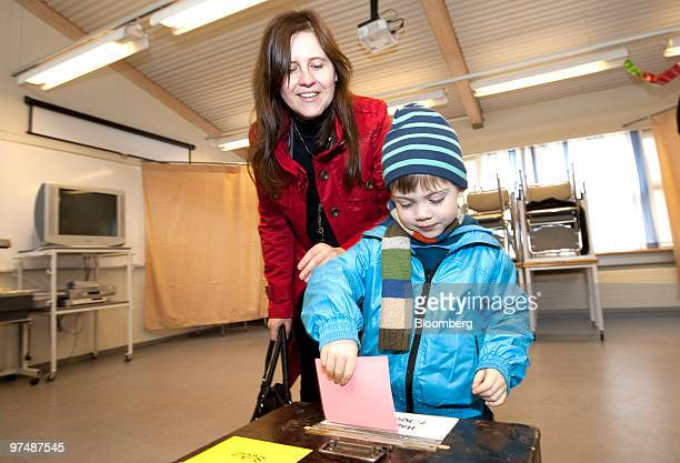 A child helps a woman cast her ballot paper in the Icelandic national referendum at a polling station in Reykjavik Iceland on Saturday March 6 2010...