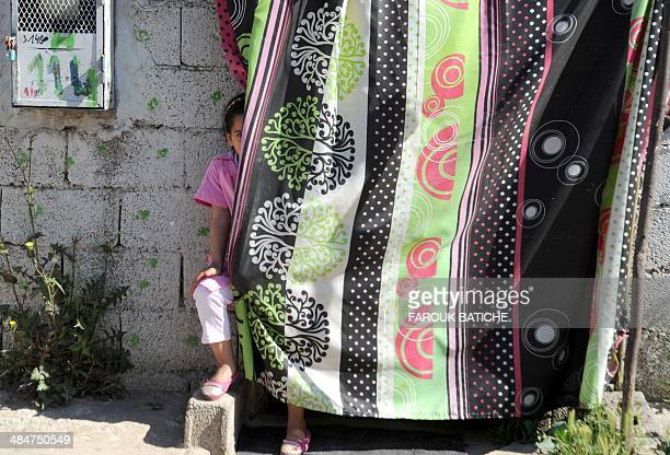 A child hides behind a curtainin the elWiam shantytown in the Djasr Kasentina Wilaya in the capital Algiers on April 9 2014 Corruption a recurring...