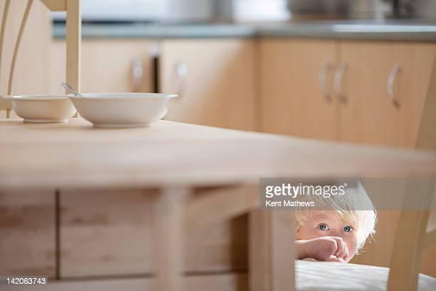 child hiding under kitchen table