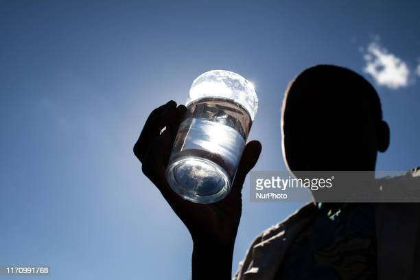 A child hold up a glass of clean drinking water in Malawi's Mongochi District It is the first time this village has ever had access to clean drinking...