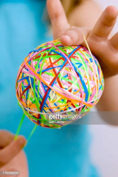Child holding a ball of colorful rubber bands