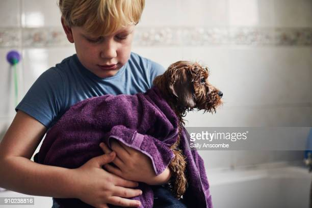 Child holding a dog in a towel