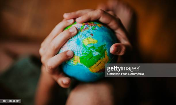 child holding a globe - global stock-fotos und bilder