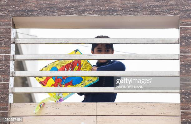 Child holding a kite watches others flying kites to celebrate Lohri, the spring festival, in Amritsar on January 13, 2021.