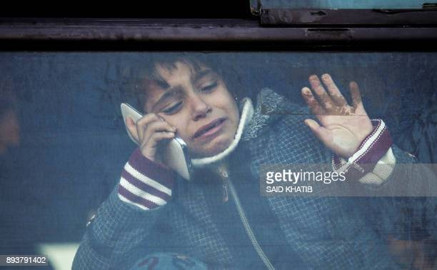Child holding a phone to her ear bids farewell through the window of a bus in Khan Younis in the southern Gaza strip on December 16, 2017 prior to...