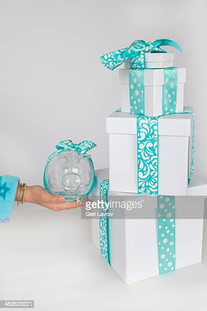 Child holding a piggy bank next to gift boxes