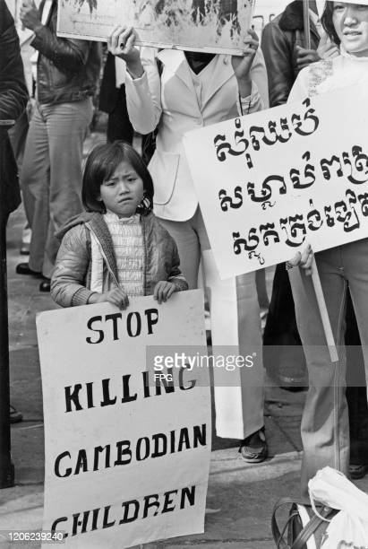 A child holding a placard which reads Stop Killing Cambodian Children at a protest against the Genocide in Cambodia perpetrated by the Khmer Rouge...