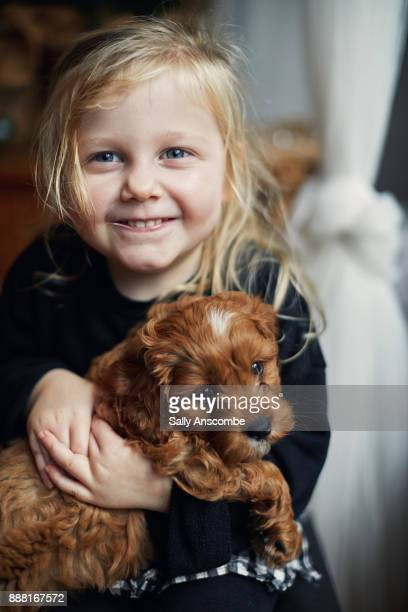Child holding a puppy